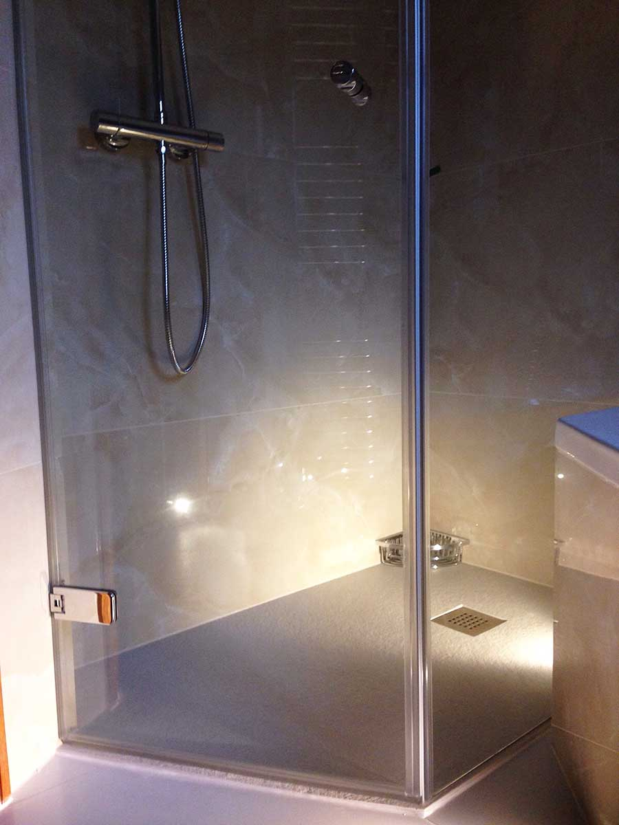 Bespoke frameless shower enclosure made to fit around a bath by Room H2o