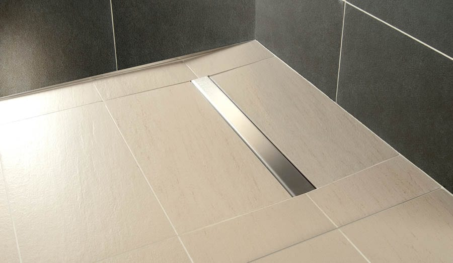 Large light coloured tiles have been used for this wetroom floor with linear drain