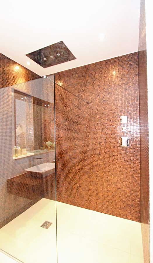A mosaic tiled luxury wet room with contrasting large sand coloured floor tiles and large frameless glass shower screen and ceiling mounted drench shower head