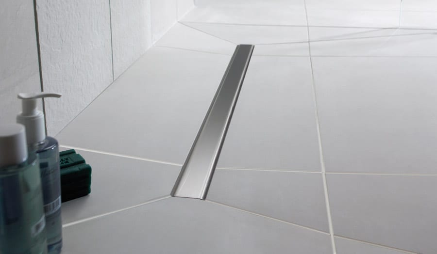 A large luxury wetroom complete with large tiles and Impey Linear stainless drain