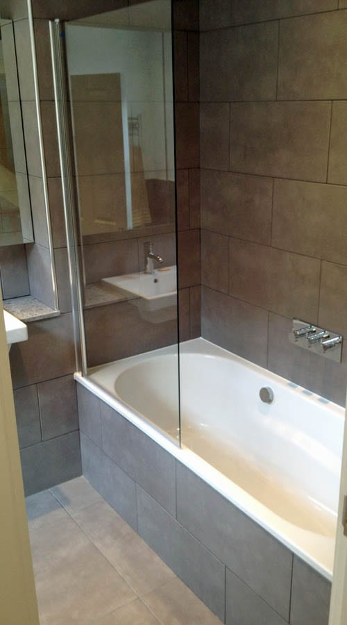A small en-suite bathroom with over bath shower and hinged bath screen designed and constructed by Room H2O