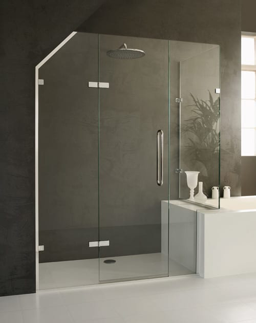 A bespoke made to measure frameless glass shower enclosure with angled top to suit a loft bathroom