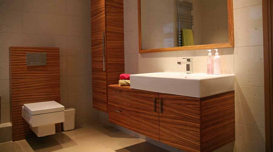 Bespoke bathroom furniture including a vanity unit with tall cupboard and cistern unit