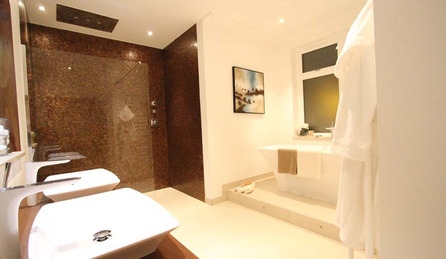 A luxury bathroom and wetroom with rust coloured mosaic and contrasting large porcelain floor tiles by Room H2O