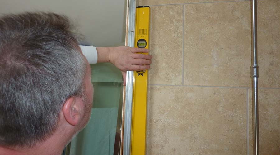 A member of the Room H2o shower survey and installation team taking measurements for a made to measure shower enclosure