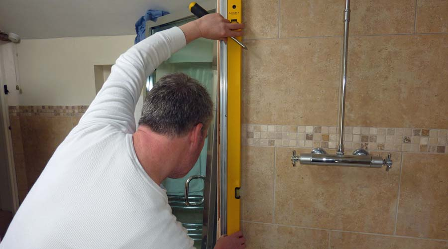 A Room H2o shower technician installing a made to measure shower enclosure