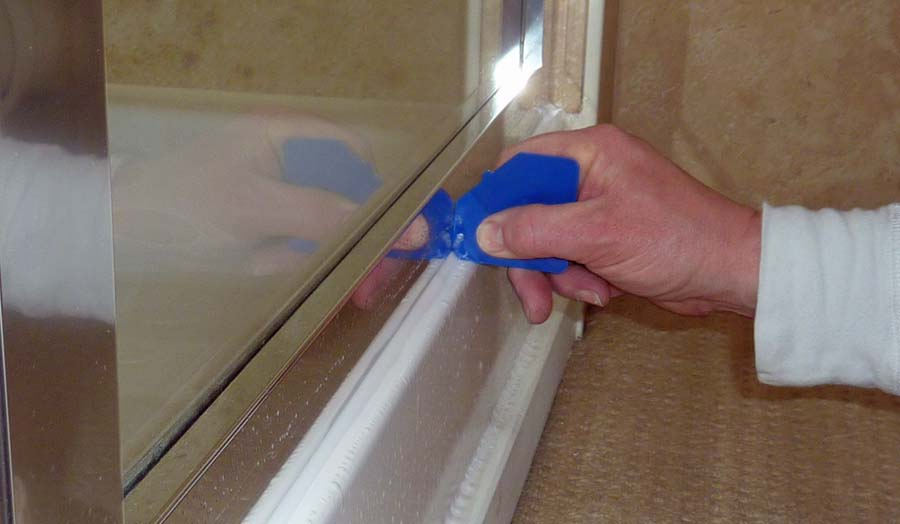 Applying silicone sealant to a shower enclosure and tray