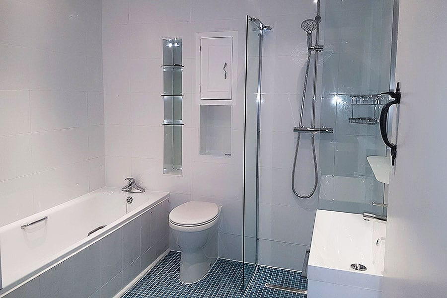 Disability bathroom with raised height toilet and wetroom show by Room H2o