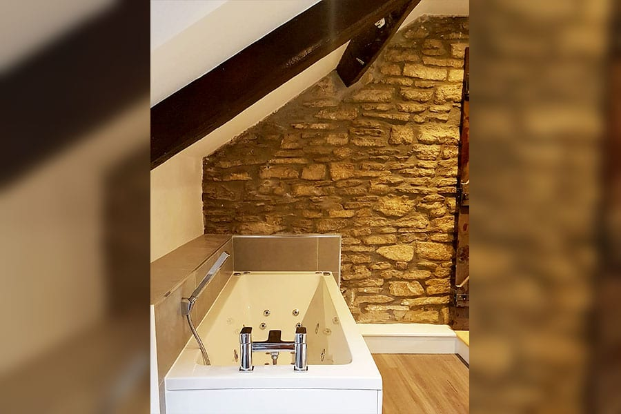 bathroom with Purbeck stone walls and support beams