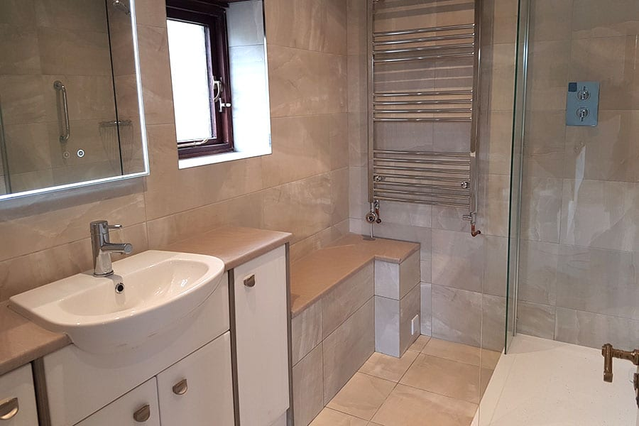 We tiled the walls of this new bathroom in Studland with Waxman Dubai Pearl porcelain tiles