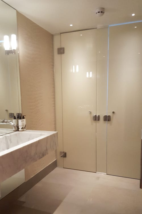Cream laminated and painted designer frameless glass toilet cubicles created by Room H2o for the Dog and Badger in Marlow