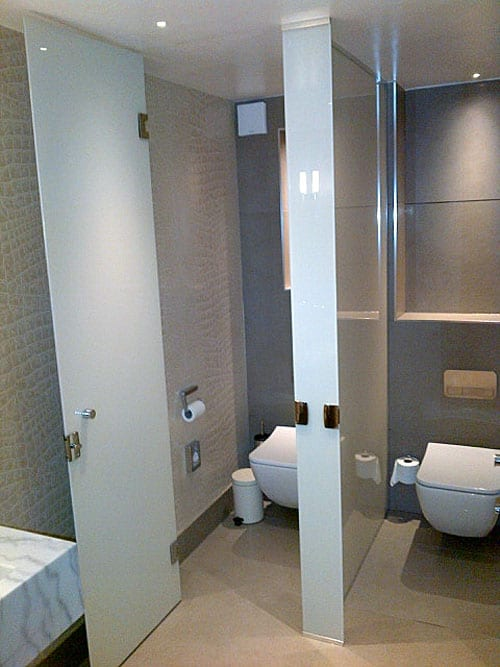 Frameless glass toilet cubicles in white painted and laminated glass by Room H2o