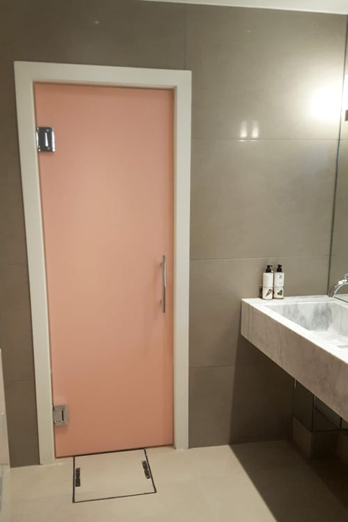 Pink laminated designer frameless glass washroom entrance door created by Room H2o for the Dog and Badger in Marlow