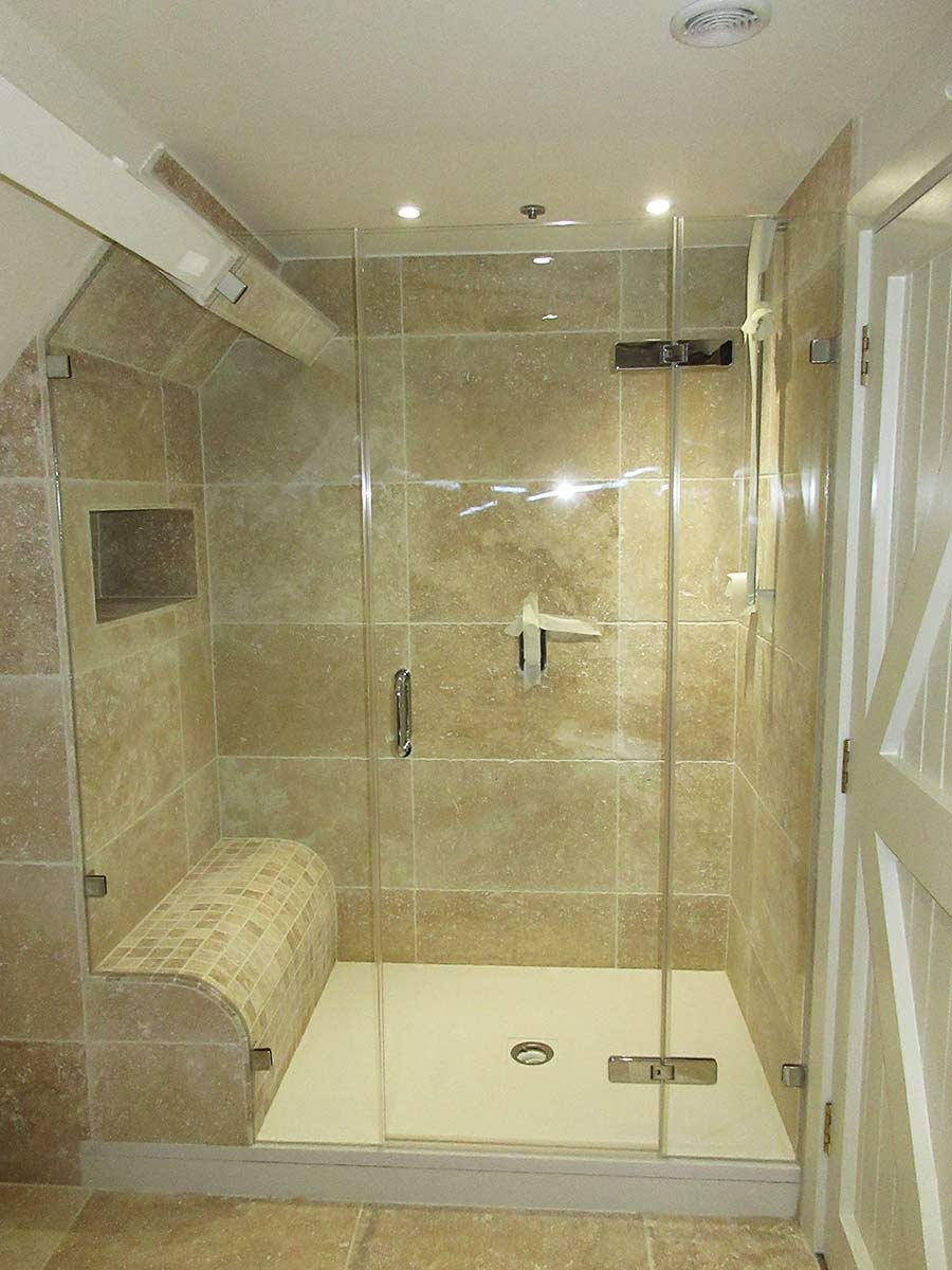 Bespoke frameless glass shower enclosure in a very awkward space featuring tiled seating area.