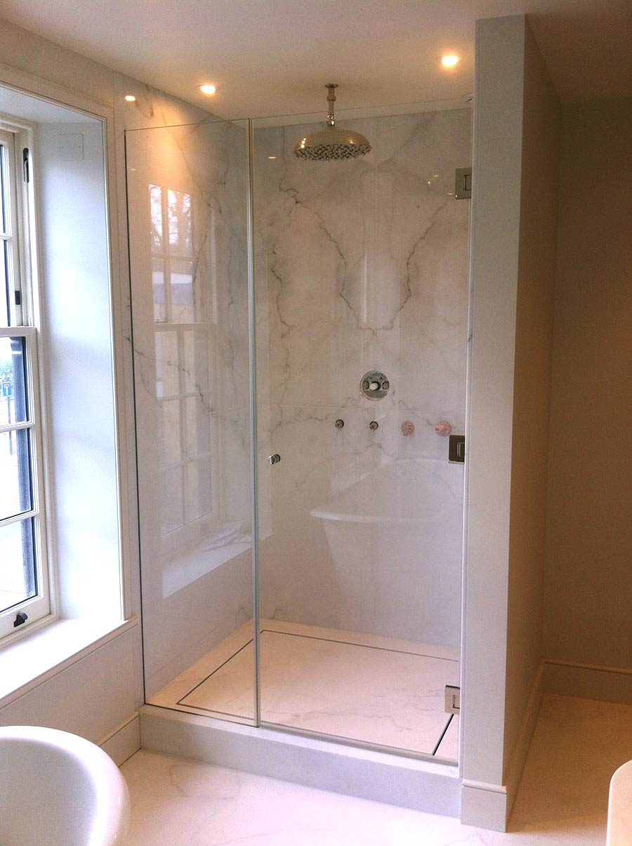 Frameless glass wall hinged shower door with glass inline panel by Room H2o