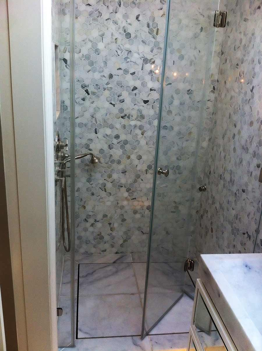 A bespoke frameless glass bifolding shower door manufactured and installed by Room H2o for a client in Chelsea