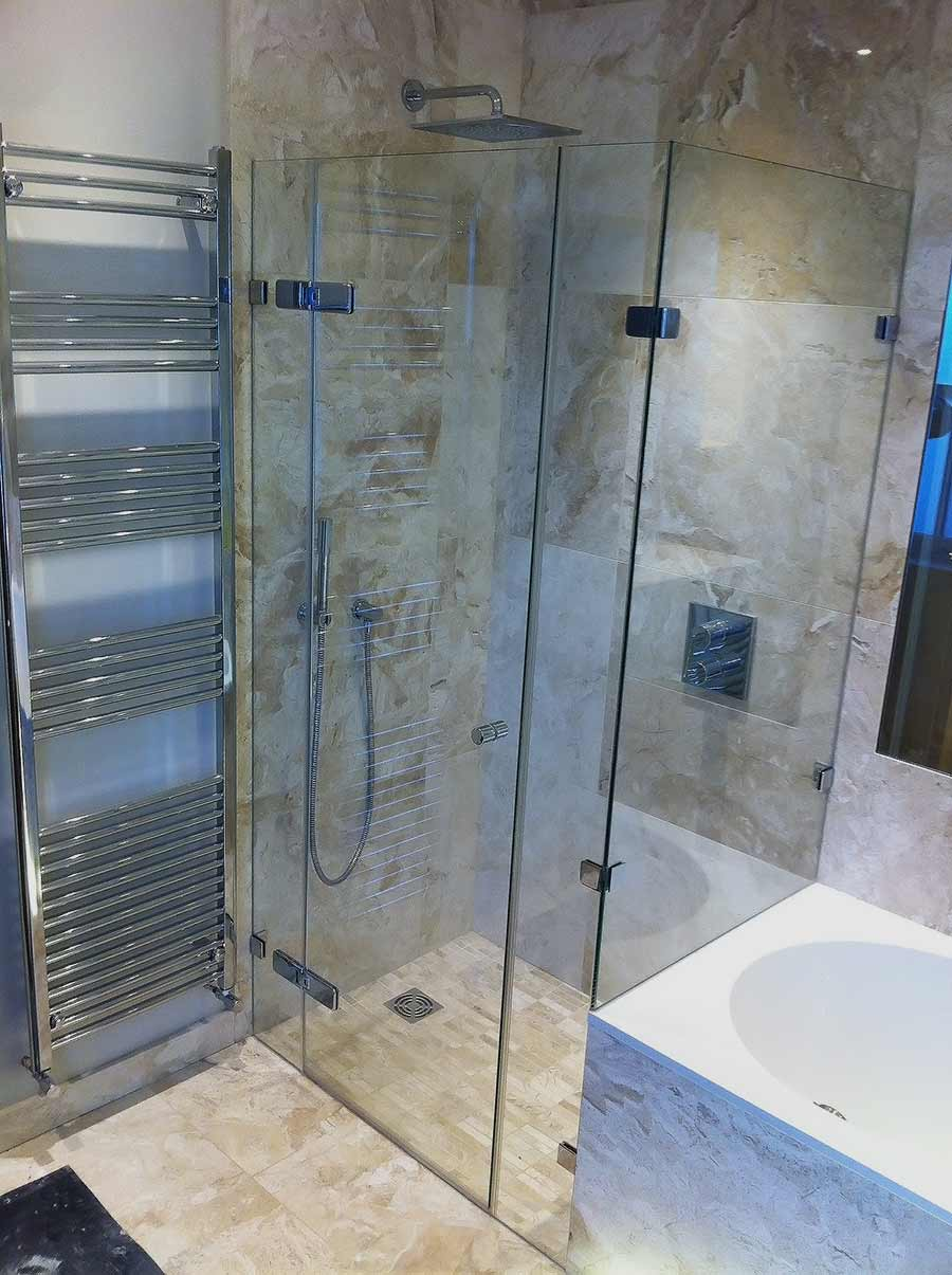 Large bespoke frameless end of bath shower enclosure with dwarf over bath panel by Room H2o