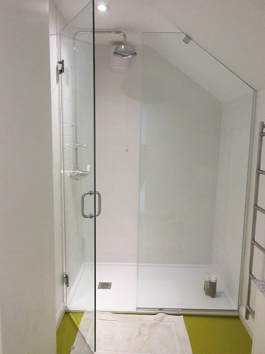Bespoke frameless shower enclosure designed and installed into a loft conversion with sloping ceilings
