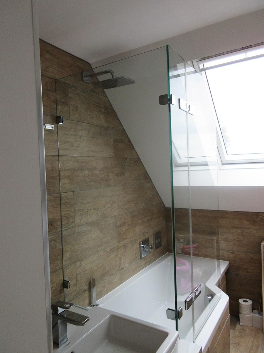 Frameless bespoke bath screen in a loft conversion with a sloping ceiling