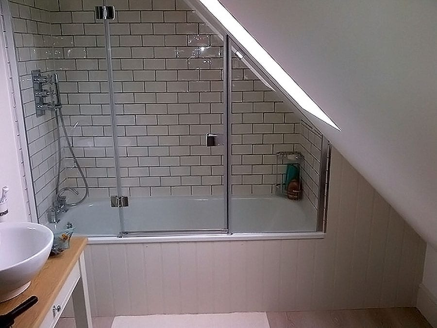 Angled semi-frameless over bath shower enclosure with hinged door by Room H2o