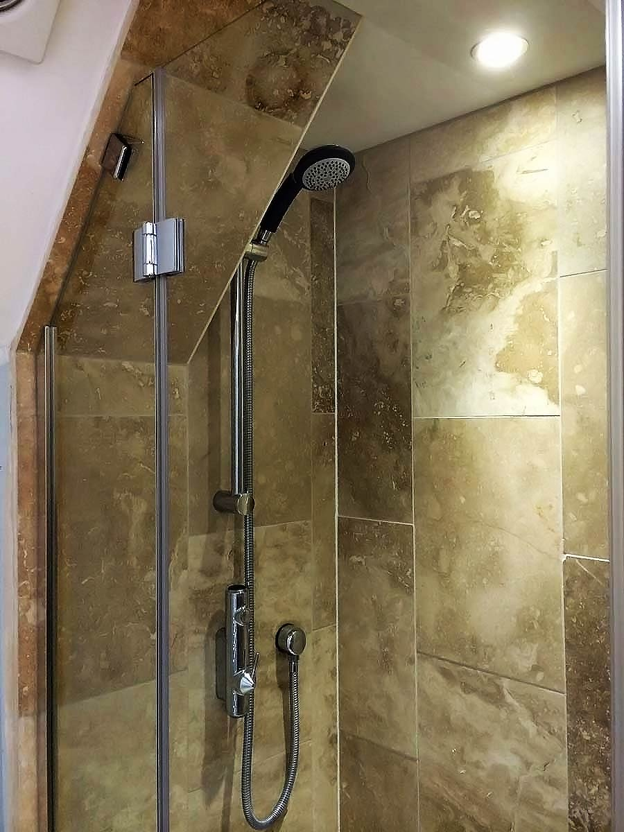 Semi-frameless inline shower enclosure with angled inline panel for a loft conversion