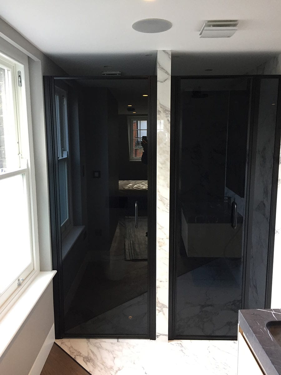 A pair of black framed glass doors made by Room H2o for a toilet and shower