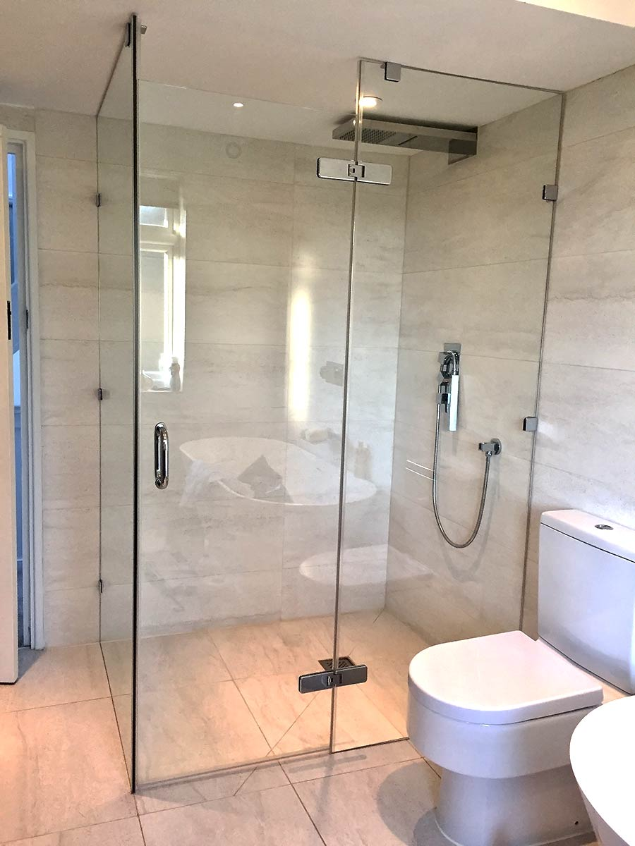 Large frameless glass wetroom shower enclosure with floor to ceiling inline and side panels with glass hinged door