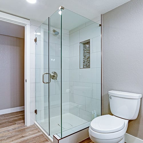 A frameless glass shower enclosure with hinged door